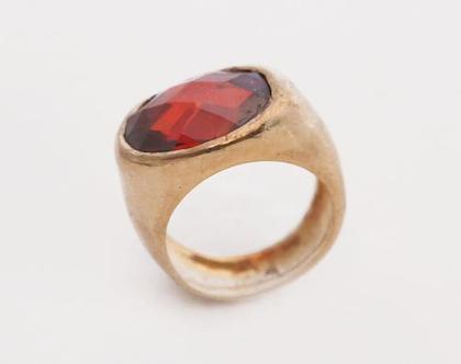 טבעת אובלית בשיבוץ אבן רובי שקועה בציפוי זהב
