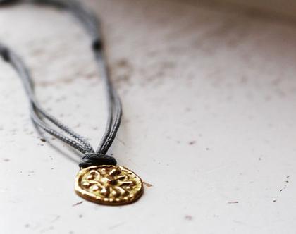 תליון מטבע זהב על חוט כותנה אפור