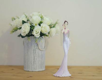 פסל אישה בשמלה ורודה
