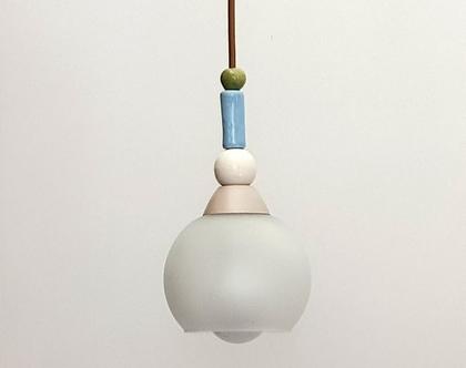 מנורה קטנה מזכוכית חלבית מעוטרת בחרוזים בצבעים עדינים ותלויה על חוט בגוון דומה לזהב