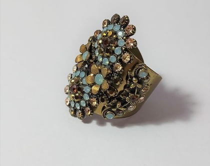 טבעת של מיכל נגרין חתומה ומרשימה משובצת בקריסטלים של סברובסקי בצבעים תורכיז וחום וצבע ברונזה הטבעת מתכווננת