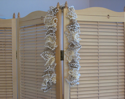צעיף רשת סרוג מסולסל בגווני בז' עם פונפונים לבנים